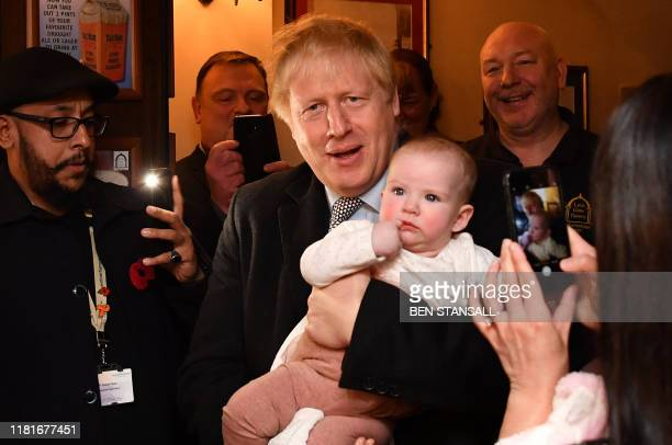 Britain's Prime Minister Boris Johnson holds a baby as he meets supporters at the Lynch Gate Tavern in Wolverhampton, central England on November 11,...