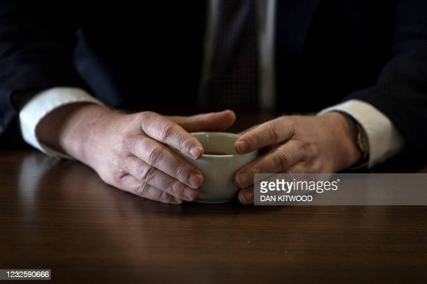 Britain's Prime Minister Boris Johnson, holds a cup of coffee as he speaks with pupils after taking part in a science lesson at King Solomon Academy...