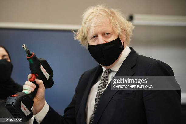 Britain's prime minister Boris Johnson holds a power tool during a visit to BAE Systems at Warton Aerodrome in Preston, northwest England, on March...