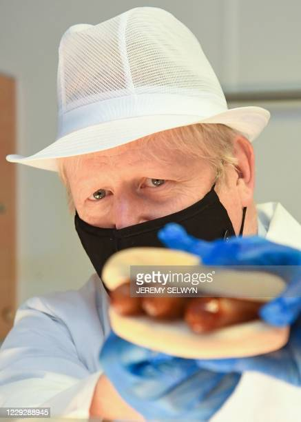 Britain's Prime Minister Boris Johnson holds a sausage butty during his visit to Royal Berkshire NHS Hospital in Reading, west of London on October...
