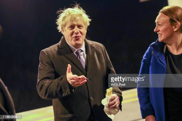 Britain's Prime Minister Boris Johnson holds a sausage roll on the platform of Milton Keynes train station, after a election campaign visit to Red...