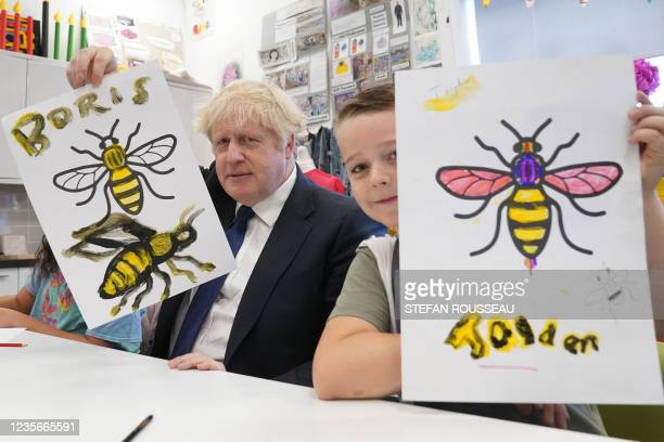 Britain's Prime Minister Boris Johnson holds up his Manchester Bee painting next to Jayden in an art class during a visit to the HideOut Youth Zone...