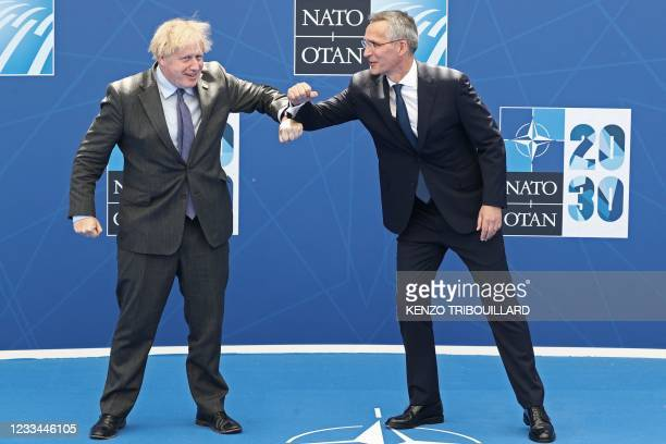 Britain's Prime Minister Boris Johnson is greeted by NATO Secretary General Jens Stoltenberg during the NATO summit at the North Atlantic Treaty...