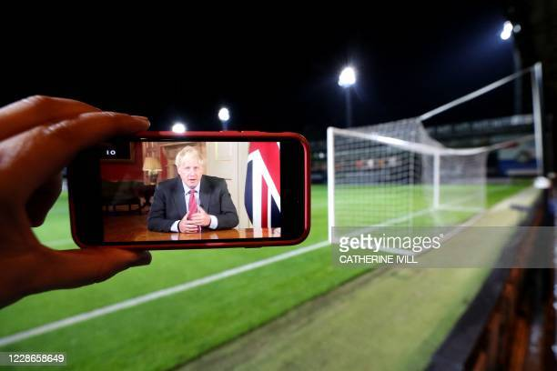 Britain's Prime Minister Boris Johnson is pictured on a mobile phone during his televised address on the latest updates of the COVID-19 pandemic,...