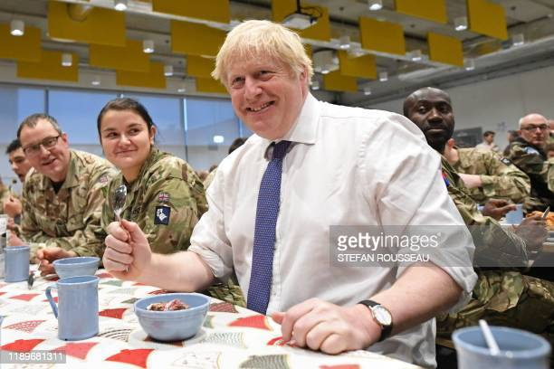 TOPSHOT Britain's Prime Minister Boris Johnson joins British troops stationed in Estonia for a meal at the Tapa military base on December 21 during a...