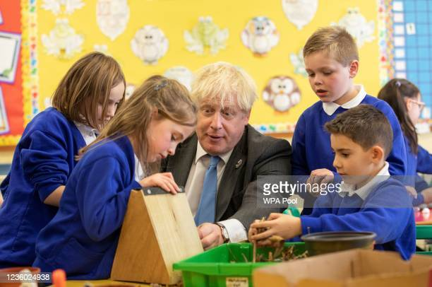 Britain's Prime Minister Boris Johnson joins schoolchildren as they make a bug hotel during a visit to Crumlin Intergrated primary school after...