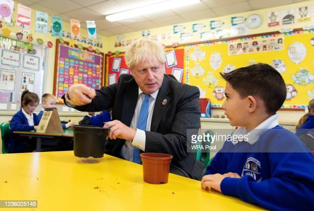 Britain's Prime Minister Boris Johnson joins schoolchildren as they plant seeds for trees during a visit to Crumlin Intergrated primary school after...