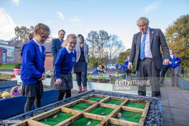 Britain's Prime Minister Boris Johnson joins schoolchildren playing a game of Tic Tac Toe in their sensory garden during a visit to Crumlin...
