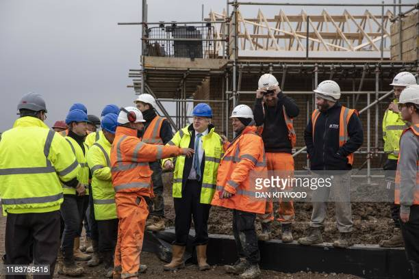 Britain's Prime Minister Boris Johnson jokes with builders during a visit to Barratt Homes's 'Willow Grove' residential housing development in...