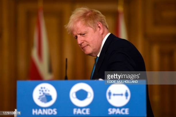 Britain's Prime Minister Boris Johnson leaves the podium at the end of the virtual press conference inside 10 Downing Street in central London on...