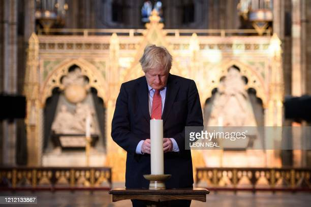 Britain's Prime Minister Boris Johnson lights a candle at the Grave of the Unknown Warrior in Westminster Abbey in London on May 7, 2020. On the eve...