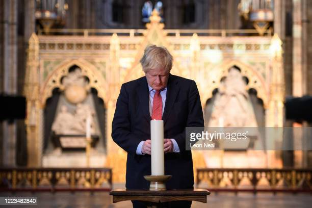 Britain's Prime Minister Boris Johnson lights a candle at the Grave of the Unknown Warrior in Westminster Abbey on May 07, 2020 in London, England....