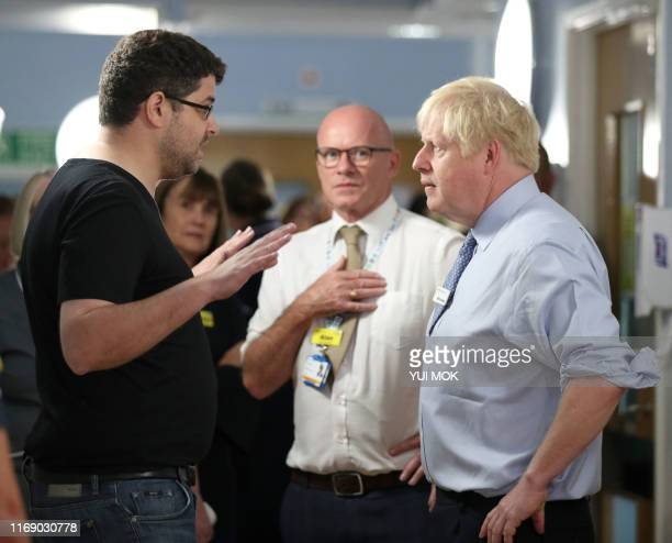 Britain's Prime Minister Boris Johnson listens as the father of a young girl who is being treated in the Acorn childrens' ward expresses his anger...