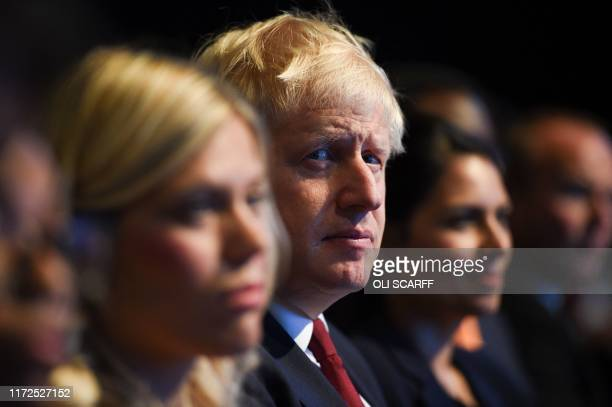 Britain's Prime Minister Boris Johnson listens to a speech by Britain's Chancellor of the Exchequer Sajid Javid in the main auditorium on the second...