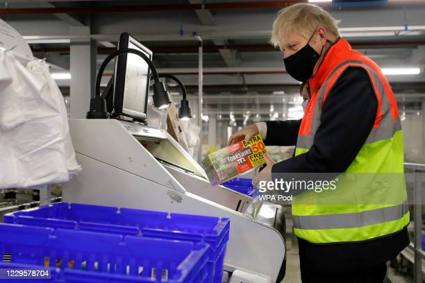 Britain's Prime Minister Boris Johnson loads produce into baskets as he visits a tescocom distribution centre on November 11 2020 in London England