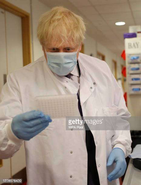 Britain's Prime Minister Boris Johnson looks at an immunological assay as he washes them during a visit to the Jenner Institute on September 18 2020...