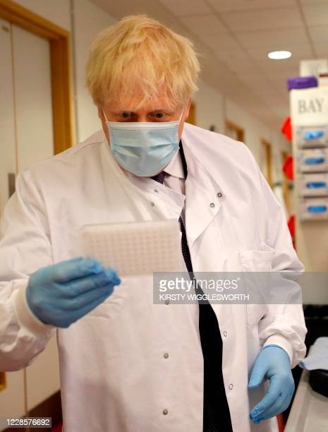 Britain's Prime Minister Boris Johnson looks at an immunological assay as he washes them during a visit to the Jenner Institute in Oxford central...