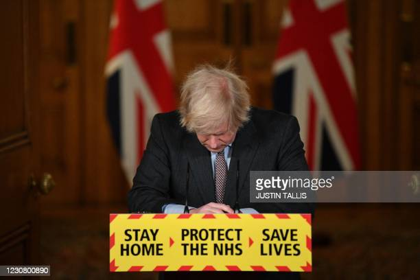 Britain's Prime Minister Boris Johnson looks down at the podium as he attends a virtual press conference on the Covid-19 pandemic, inside 10 Downing...