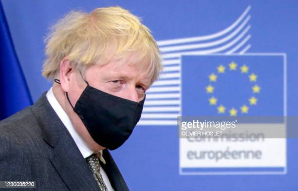 Britain's Prime Minister Boris Johnson looks on as he is welcomed by European Commission President in the Berlaymont building at the EU headquarters...
