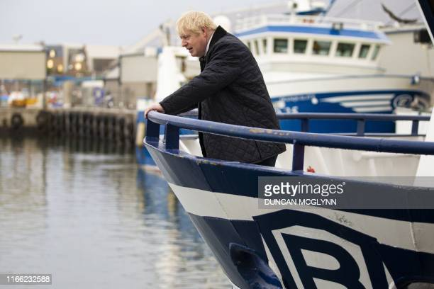 Britain's Prime Minister Boris Johnson looks on from aboard the Opportunis IV fishing trawler during a visit to Peterhead in Scotland on September 6...