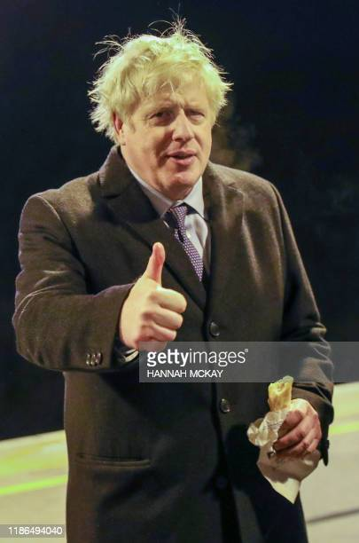 Britain's Prime Minister Boris Johnson makes a thumbs up gesutre while holding a sausage roll, on the platform of Milton Keynes train station in...