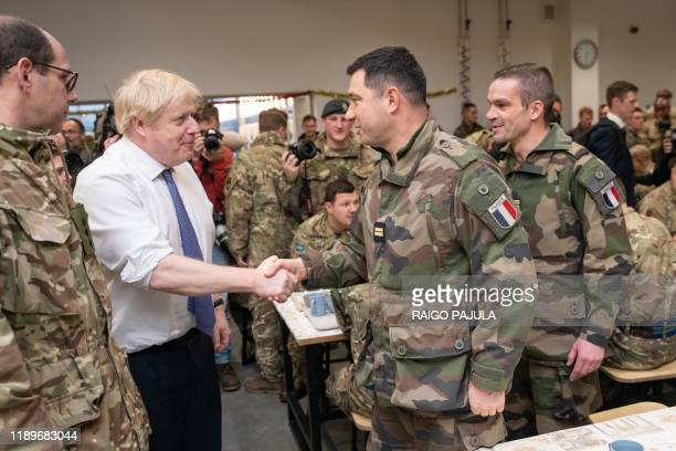 Britain's Prime Minister Boris Johnson meets British troops stationed in Estonia for a meal at the Tapa military base on December 21 during a oneday...