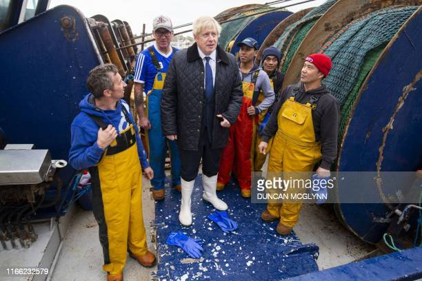 Britain's Prime Minister Boris Johnson meets crew aboard the Opportunis IV fishing trawler during a visit to Peterhead in Scotland on September 6...