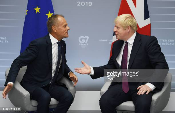 Britain's Prime Minister Boris Johnson meets European Union Council President Donald Tusk at a bilateral meeting during the G7 summit on August 25,...