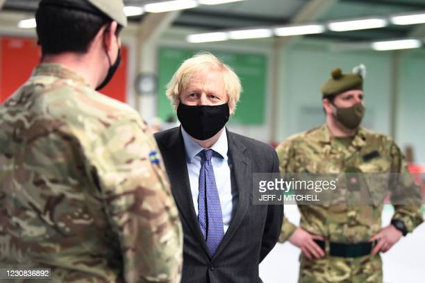 Britain's Prime Minister Boris Johnson meets troops as they set up a vaccination centre in the Castlemilk district in Glasgow, Scotland on January 28...