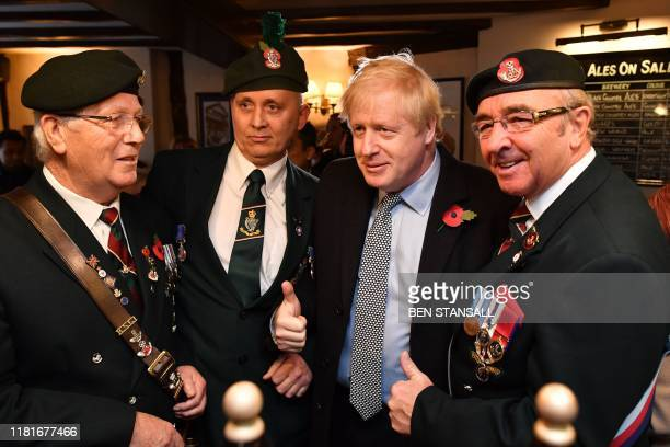 Britain's Prime Minister Boris Johnson meets veterans at the Lynch Gate Tavern in Wolverhampton central England on November 11 2019 while on the...