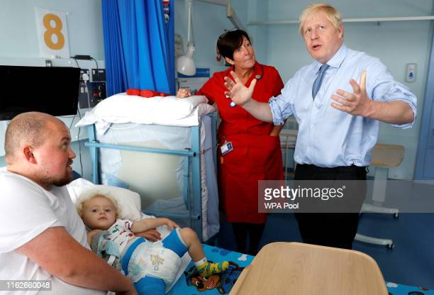 Britain's Prime Minister Boris Johnson meets with patient patient Logan Rock during his visit to the Royal Cornwall Hospital on August 19 2019 in...