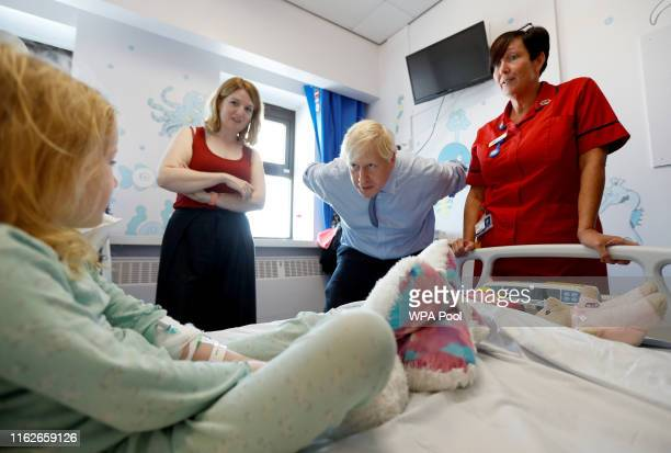 Britain's Prime Minister Boris Johnson meets with patient Scarlett Gibbons during his visit to the Royal Cornwall Hospital on August 19 2019 in Truro...