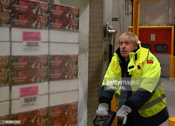 Britain's Prime Minister Boris Johnson moves a pallet of chocolate cake in a 25 degree celsius storage unit during a general election campaign visit...