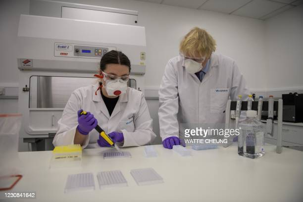 Britain's Prime Minister Boris Johnson observes quality control technician Kerri Symington as he visits the French biotechnology laboratory Valneva...