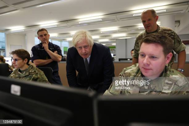 Britain's Prime Minister Boris Johnson observes the operations room for the Afghan Relocation and Assistance Policy as he visits Northwood...