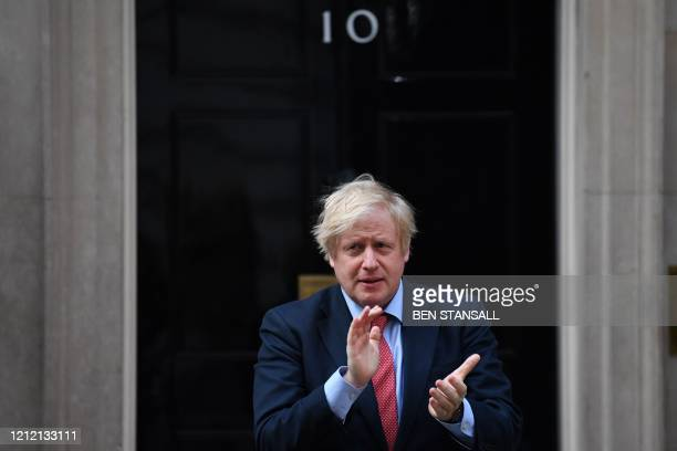 "Britain's Prime Minister Boris Johnson participates in a national ""clap for carers"" to show thanks for the work of Britain's NHS workers and other..."