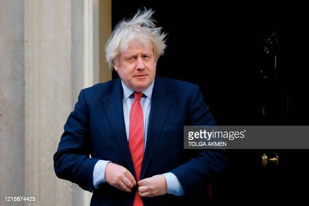 """Britain's Prime Minister Boris Johnson participates in a national """"clap for carers"""" to show thanks for the work of Britain's NHS workers and other..."""