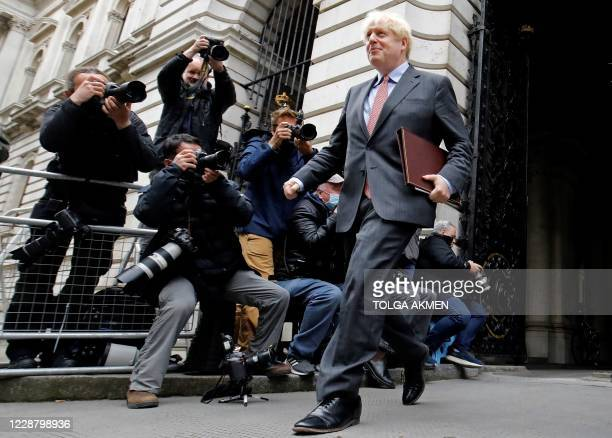 Britain's Prime Minister Boris Johnson passes photographers as he returns to Downing Street after attending the weekly cabinet meeting at the Foreign...