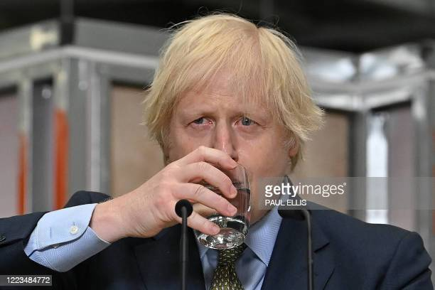 Britain's Prime Minister Boris Johnson pauses for a drink during his speech during his visit to Dudley College of Technology in Dudley, central...