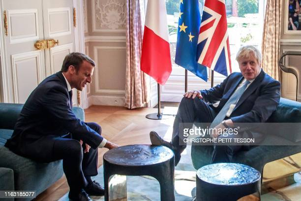 TOPSHOT Britain's Prime Minister Boris Johnson places his foot on the table during a meeting with French President Emmanuel Macron at the Elysee...