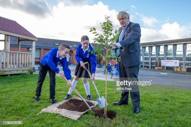 Britain's Prime Minister Boris Johnson plants a tree with help from P7 pupils Sophie and Oscar during a visit to Crumlin Intergrated primary school...