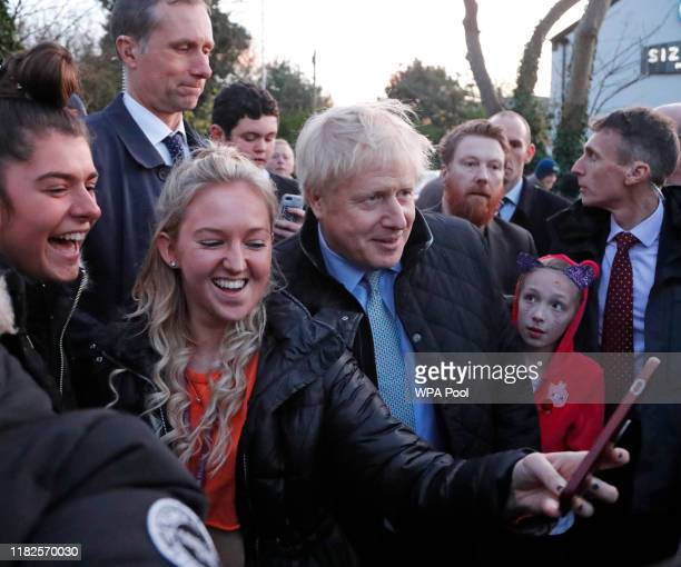 Britain's Prime Minister Boris Johnson poes for a picture during a General Election campaign trail stop at ThorntonCleveleys railway station on...
