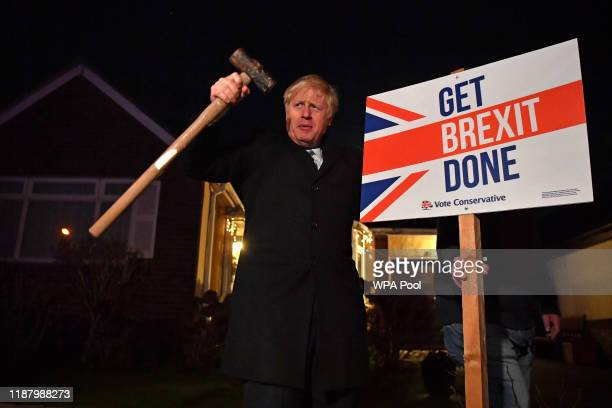 "Britain's Prime Minister Boris Johnson poses after hammering a ""Get Brexit Done"" sign into the garden of a supporter during a campaign stop on the..."