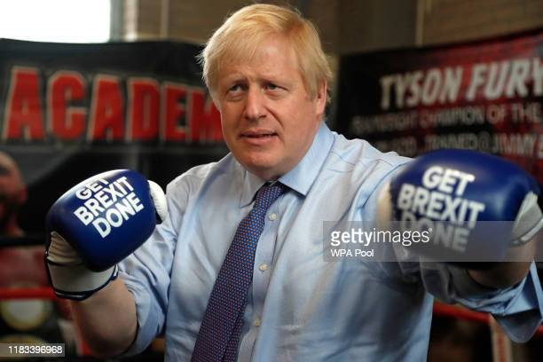 """Britain's Prime Minister Boris Johnson poses for a photo wearing boxing gloves emblazoned with """"Get Brexit Done"""" during a stop in his General..."""