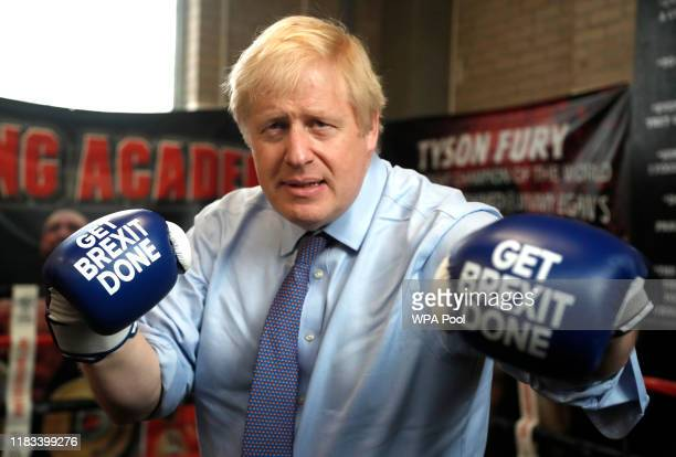 "Britain's Prime Minister Boris Johnson poses for a photo wearing boxing gloves emblazoned with ""Get Brexit Done"" during a stop in his General..."