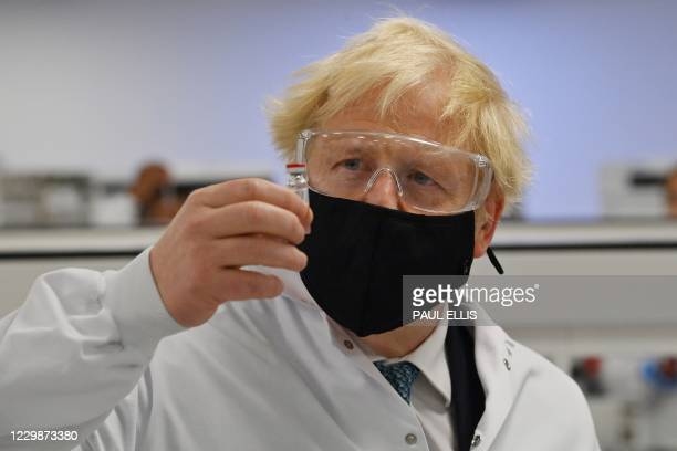 Britain's Prime Minister Boris Johnson poses for a photograph with a vial of the AstraZeneca/Oxford University COVID-19 candidate vaccine, known as...