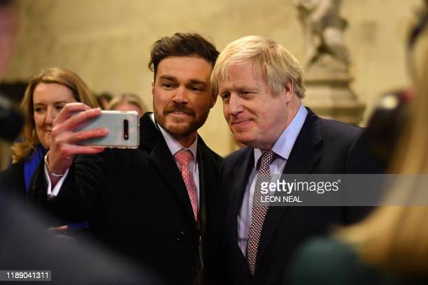 Britain's Prime Minister Boris Johnson poses for a selfie as he greets newlyelected Conservative MPs in the Palace of Westminster central London on...