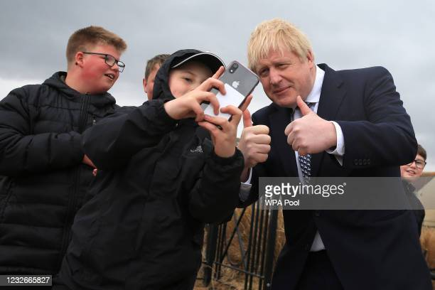 Britain's Prime Minister, Boris Johnson poses for a 'selfie' photograph as he meets members of the public while campaigning on behalf of Conservative...