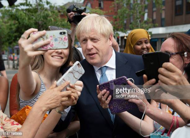 Britain's Prime Minister Boris Johnson poses for selfie photographs with members of the public as he takes a walkabout with Britain's Home Secretary...