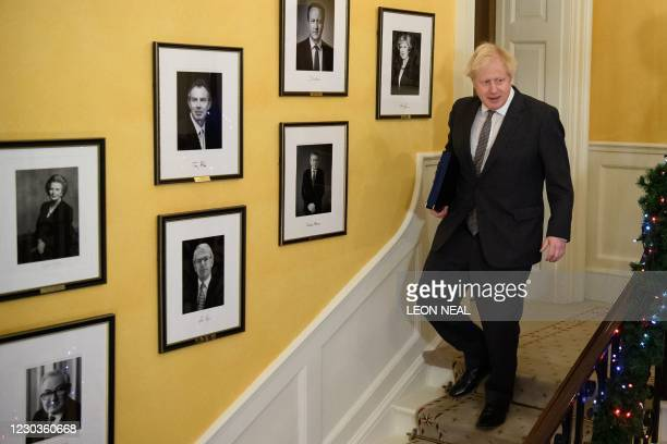 Britain's Prime Minister Boris Johnson poses on the stairs after signing the Trade and Cooperation Agreement between the UK and the EU, the Brexit...